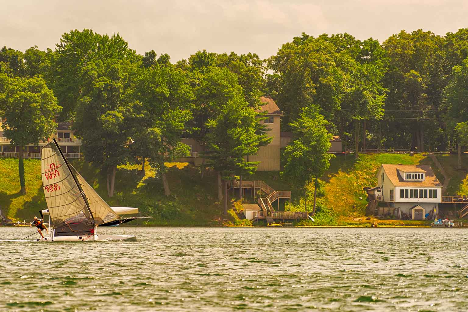 A sailboat glides by houses